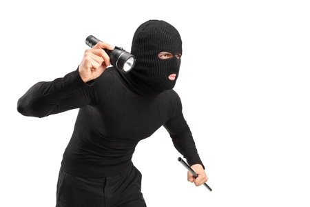 A thief holding a flashlight and piece of pipe isolated on white background photo