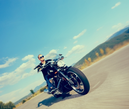 Biker riding a customized motorcycle on an open road shot with a tilt and shift lens and with very shallow depth of field photo
