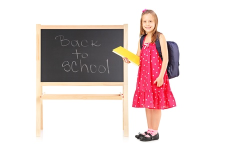 Full length portrait of a schoolgirl holding a notebook and posing next to a board isolated on white background photo