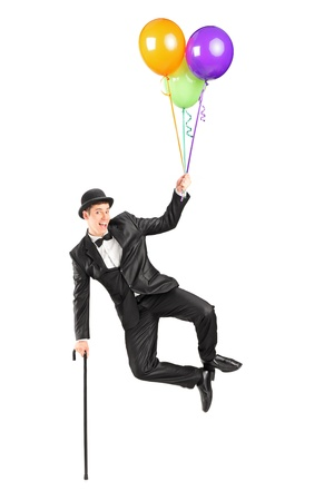 Magician flying up in the air and holding balloons isolated on white background photo
