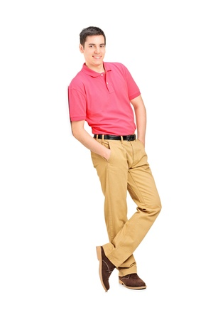 leaning against: Full length portrait of a smiling man leaning against wall, isolated on white background