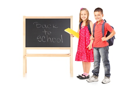 book bags: Full length portrait of schoolgirl and boy posing next to a board isolated on white background