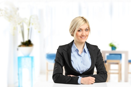 A blond smiling businesswoman sitting at her desk photo