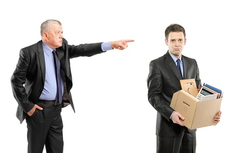 fired: An angry boss firing a man carrying a box of personal items isolated on white background Stock Photo