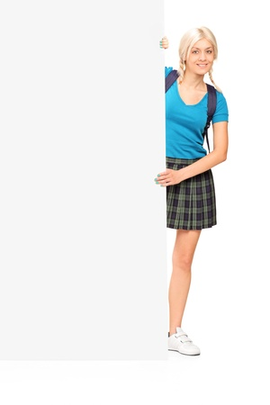 Full length portrait of a female student posing behind a blank panel isolated on white background Stock Photo - 14699545