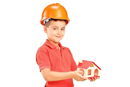A child with helmet holding a model of house isolated on white background Stock Photo - 14699475