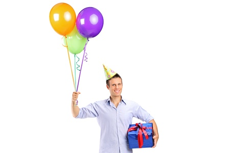 A smiling young man holding a present and baloons isolated on white Stock Photo - 14699492