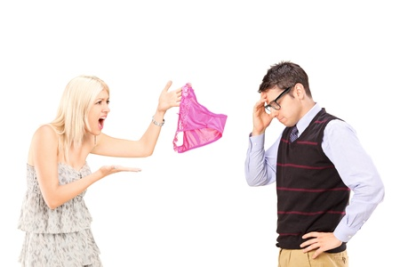 boy underwear: Angry girlfriend shouting at her boyfriend and holding female knickers isolated on white background Stock Photo