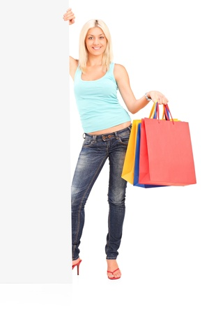 Full length portrait of a female holding shopping bags and standing next to a white panel Stock Photo - 14796141