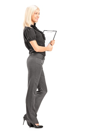 Full length portrait of a young professional woman holding a clipboard, isolated on white background photo
