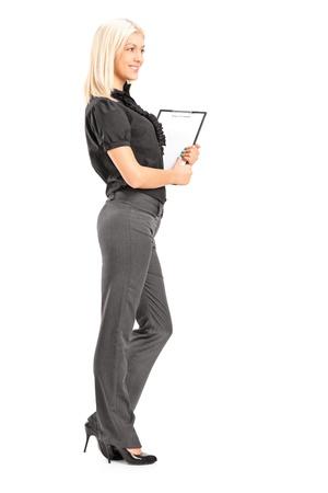 Volle Länge Porträt einer jungen professionellen Frau hält eine Zwischenablage, isoliert auf weißem Hintergrund