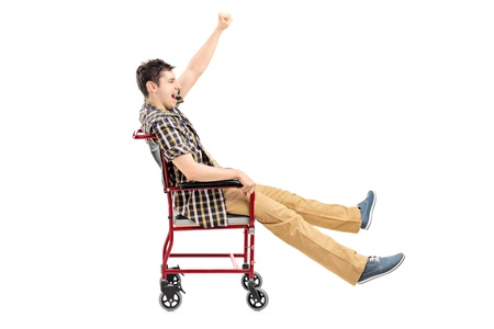 joking: Happy young man sitting in a wheelchair and gesturing isolated on white background