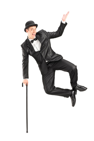 Magician jumping and holding a cane, isolated on white background photo