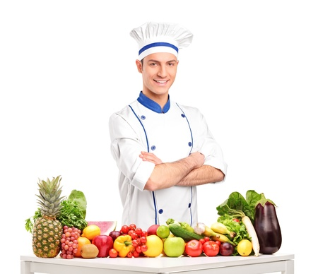 fruit stand: Male chef with fruits and vegetables on table, isolated on white background