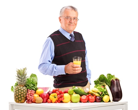 Mature man holding a glass of juice and standing next to fruits and vegetables, isolated on white background photo