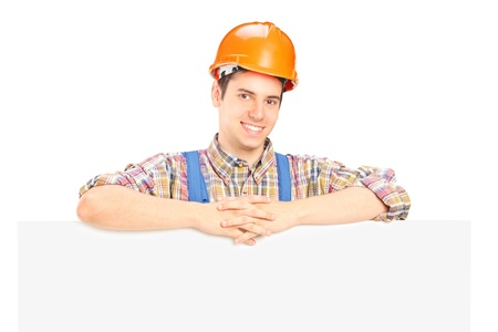 Satisfied male construction worker standing behind white panel photo