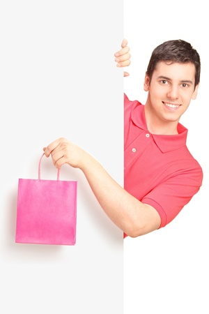 Young male holding a pink bag and standing behind white panel photo