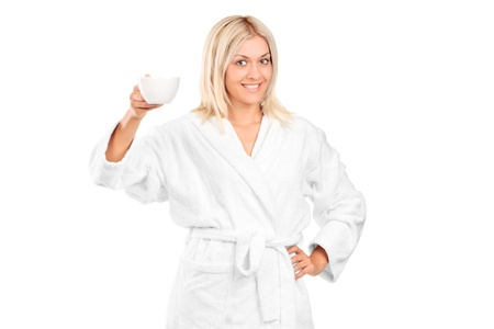 A blond woman in bathrobe holding a coffee cup isolated against white background photo