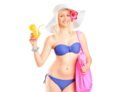 An attractive blond woman in swimsuit holding a cocktail isolated against white background photo