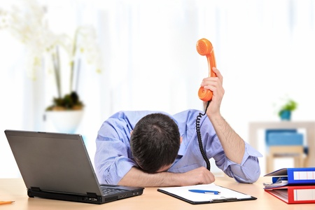 Een uitgeputte zakenman die een telefoon in zijn kantoor