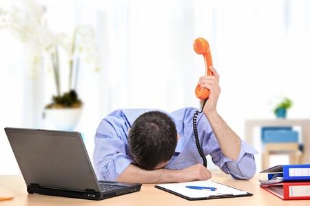agotado: Un hombre de negocios agotado que sostiene un teléfono en su oficina