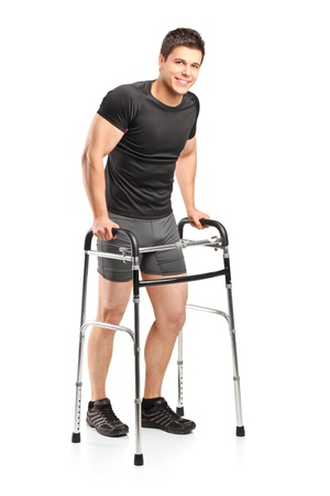 Full length portrait of a young smiling athlete using a walker isolated on white background photo