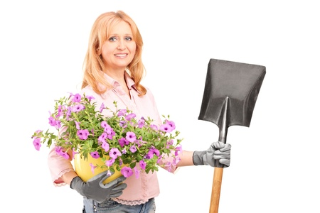 horticulturist: A female gardener holding  flowers and a shovel isolated on white background