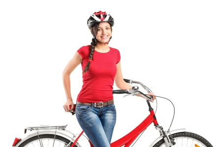 A smiling female posing next to a bicycle isolated on white background photo