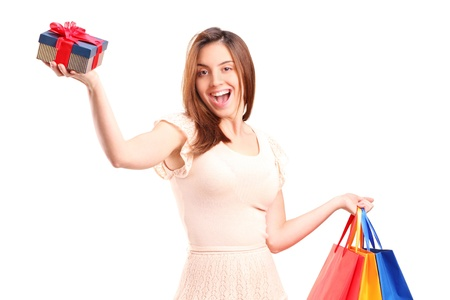 A smiling woman holding a shopping bags and a gift isolated on white background photo