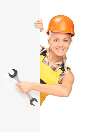 Female construction worker holding a wrench, standing behind white panel photo