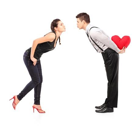 beso: Retrato de cuerpo entero de una joven pareja heterosexual a punto de besar aisladas sobre fondo blanco