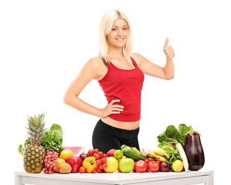 Healthy smiling woman with fruits and vegetables giving a thumb up isolated on white background Stock Photo - 14882078