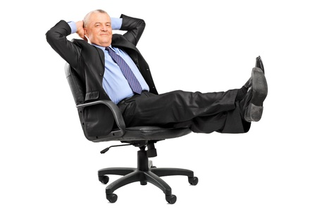 carelessness: Mature businessman resting in armchair with legs up isolated on white background Stock Photo