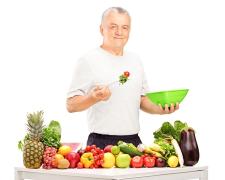 Mature man eating a salad, with fruits and vegetables on a table photo