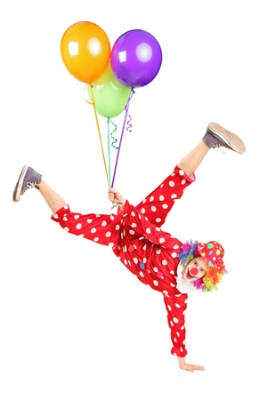 Clown holding balloons and standing on one hand isolated on white background Stock Photo