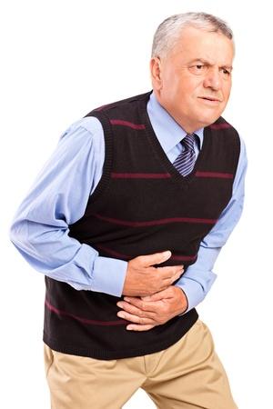dolor abdominal: Hombre maduro abrumado por un dolor en el estómago aislados en fondo blanco Foto de archivo