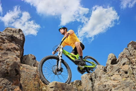 extreme angle: Person riding a mountain bike amid rocks on a sunny day against a blue sky and clouds, low angle view Stock Photo