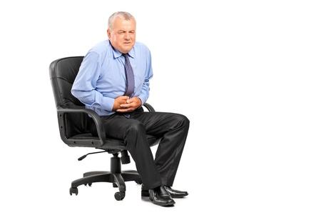 dolor de estomago: Hombre de negocios que tiene un dolor de est�mago aislado sobre fondo blanco Foto de archivo