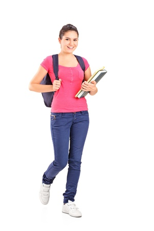 adolescence: Full length portrait of a female student holding books isolated on white