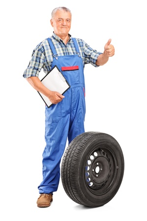 Full length portrait of a mature mechanic with tyre isolated on white background Stock Photo - 15203003