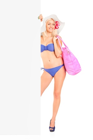 Full length portrait of a woman in bikini standing and holding a white panel isolated on white photo