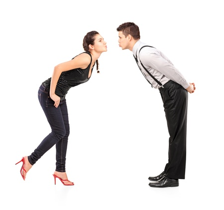 kissing couple: Full length portrait of a young heterosexual couple about to kiss isolated against white background