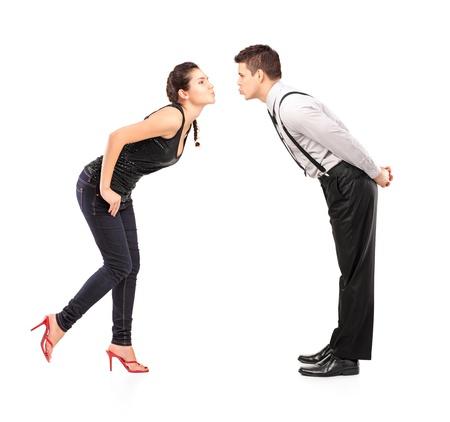 enamorados besandose: Retrato de cuerpo entero de una joven pareja heterosexual a punto de besar aisladas contra el fondo blanco Foto de archivo