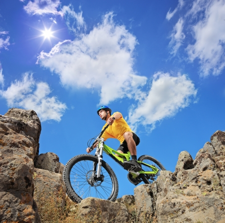 extreme angle: Person riding a mountain bike a mid rocks on a sunny day against a blue sky and clouds, low angle view