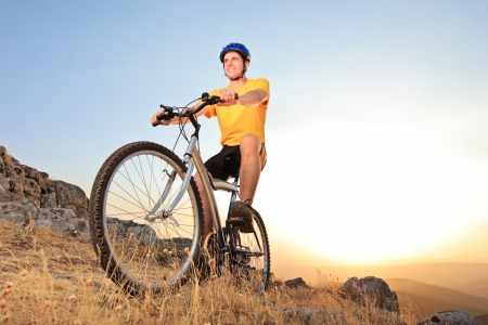 Person riding a mountain bike on a sunset, low angle view photo