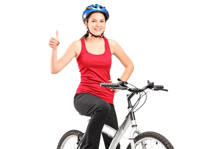 A bicyclist posing on a bicycle and giving a thumb up isolated against white background photo