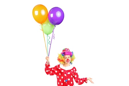 A female clown, happy joyful expression on face, with a bunch of balloons isolated on white background photo