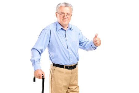 A senior man holding a cane and giving thumb up isolated on white background Stock Photo - 14943089