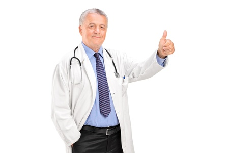 A smiling mature healthcare professional giving a thumb up isolated on white background photo