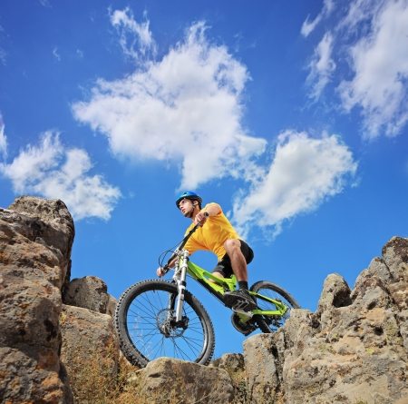 helmet bike: A person riding a mountain bike on a sunny day, low angle view